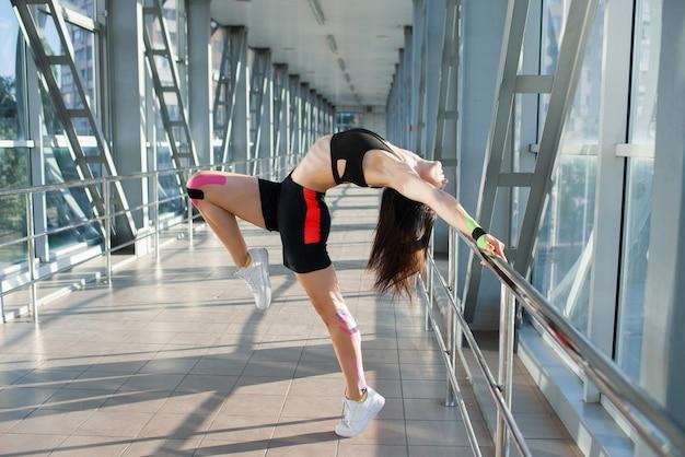 Gemnastics 포즈를 연습 근육 갈색 머리 여자의 측면보기. 젊은 유연한 여성 운동 선수 지주 난간 실내, 몸에 다채로운 kinesiotaping, 미래 지향적 인 인테리어 포즈.
