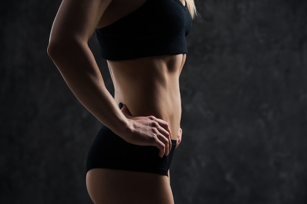 立っている筋肉フィットネス女性モデルの側面図