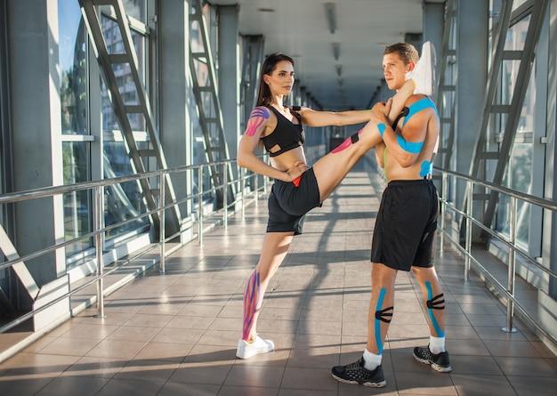 남자의 어깨에 다리를 들고 분할 연습 근육 유연한 갈색 머리 여자의 측면보기. 실내 훈련 젊은 부부 선수, 몸에 다채로운 kinesiotaping, 미래 지향적 인 인테리어.