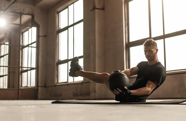 Вид сбоку мускулистого спортсмена, выполняющего упражнения на пресс с мячом во время интенсивной фитнес-тренировки в тренажерном зале