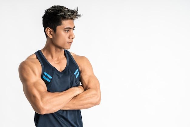 Вид сбоку мускулистого мужчины, стоящего в спортивной одежде со скрещенными руками, смотрит в сторону