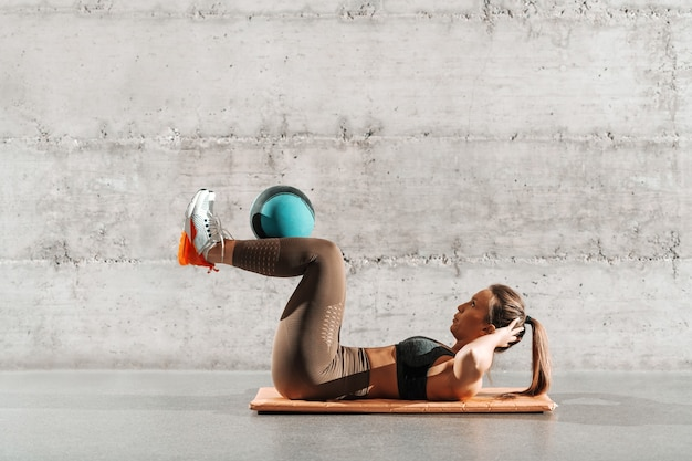 ポニーテールと灰色の壁の前にマットの上のボールと腹筋をしているスポーツウェアで筋肉の強力な女性の側面図です。