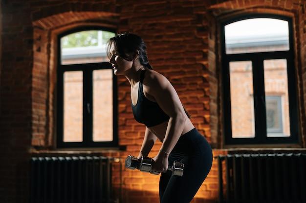 아령으로 운동을 하 고 운동복을 입고 아름 다운 강한 몸을 가진 근육 질의 젊은 운동 여자의 측면 보기. 어두운 체육관에서 운동하는 백인 피트니스 여성 운동.