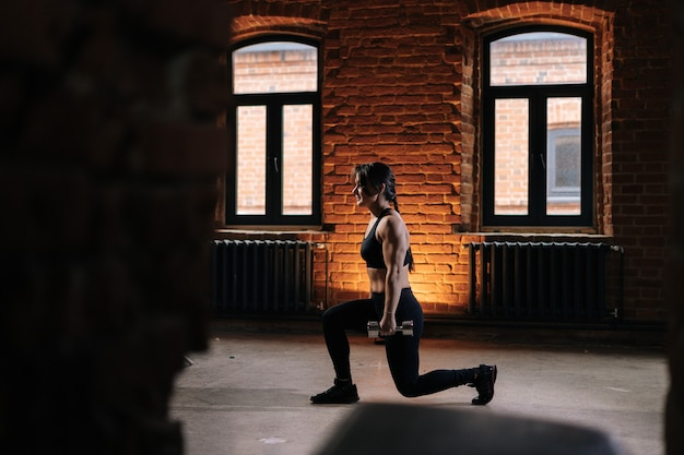 スクワットをし、ダンベルを保持しているスポーツウェアを身に着けている美しい強い体を持つ筋肉の若い運動女性の側面図。暗いジムで運動する白人フィットネス女性のトレーニング。