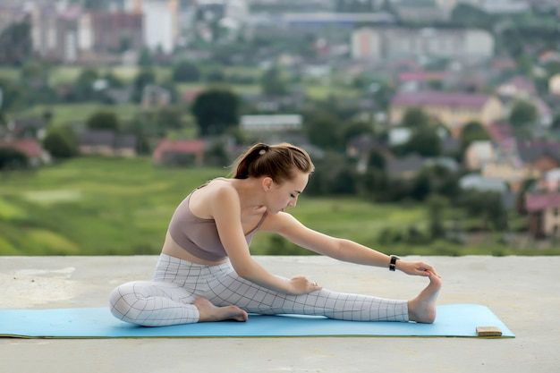 Вид сбоку мышечной молодой женщины с длинным хвостом в солнечное утро. великолепная девушка делает упражнения, разогревая нижнюю часть тела по городу.