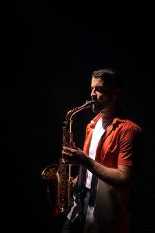 Вид сбоку музыканта, играющего на саксофоне с копией пространства