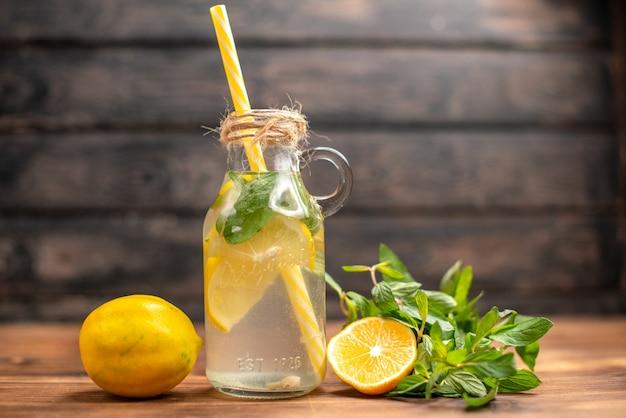 Вид сбоку на натуральную свежую воду для детоксикации с мятой и апельсином в трубке на коричневом фоне Бесплатные Фотографии