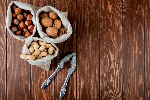 コピースペースを持つ木製の背景にナッツクラッカーとシェルで袋クルミピーナッツとヘーゼルナッツのナッツの側面図