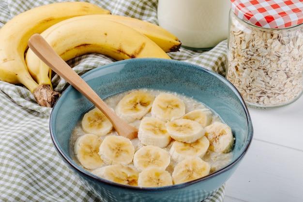 Вид сбоку овсяной каши с бананом в керамической миске на деревенском столе