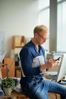 Вид сбоку офисного клерка, проверяющего его телефон перед кратким собранием