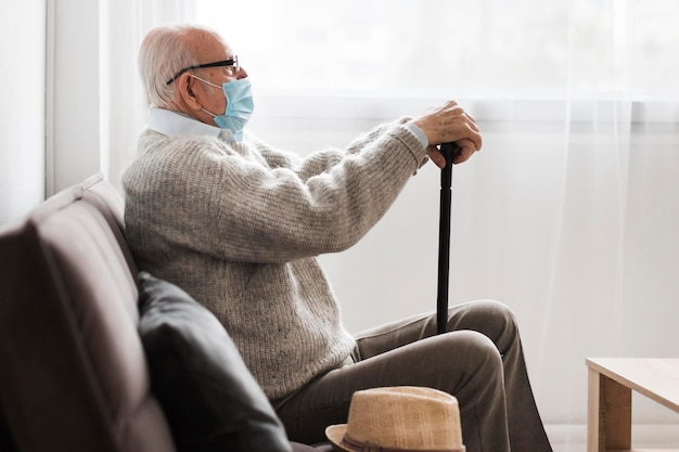Вид сбоку старика с медицинской маской в доме престарелых