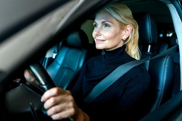 車を運転する古いビジネス女性の側面図