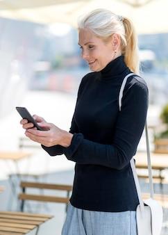 Вид сбоку пожилой деловой женщины на смартфоне на открытом воздухе