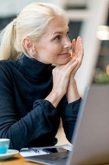 Вид сбоку пожилой деловой женщины, работающей на ноутбуке, наслаждаясь кофе