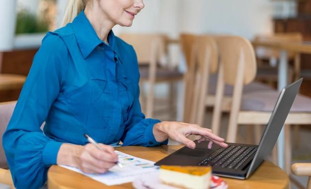 Вид сбоку пожилой деловой женщины, работающей на ноутбуке с бумагами