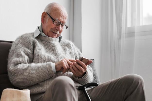 Вид сбоку пожилого мужчины в доме престарелых с помощью смартфона