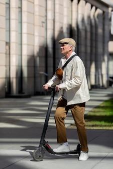 Вид сбоку пожилого человека в городе, едущего на электросамокате
