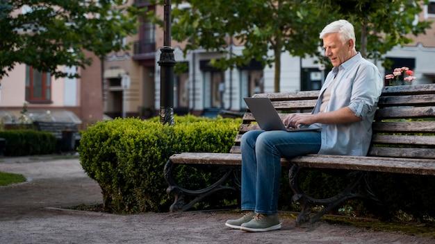 Вид сбоку пожилого человека на открытом воздухе на скамейке с ноутбуком