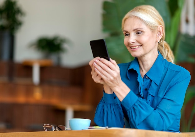 Вид сбоку пожилой женщины, держащей смартфон и улыбающейся