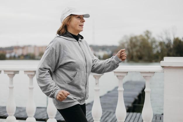 屋外でジョギングしている年上の女性の側面図