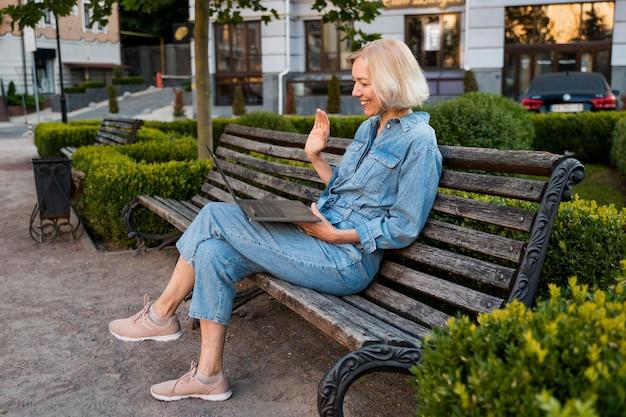 Вид сбоку пожилой женщины на открытом воздухе на скамейке, размахивая ноутбуком