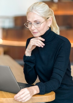 Вид сбоку пожилой женщины в очках и работающей на ноутбуке