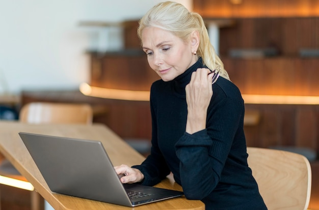 Вид сбоку пожилой женщины в очках, работающих на ноутбуке