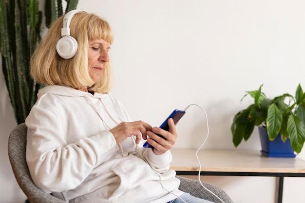 Вид сбоку пожилой женщины с наушниками с помощью смартфона