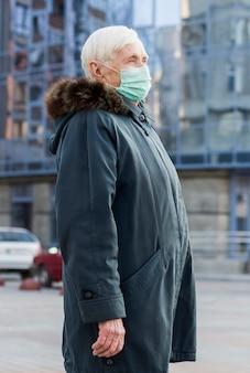 都市の医療マスクを持つ年上の女性の側面図