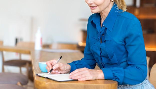 Вид сбоку пожилой женщины с ручкой и работой ноутбука