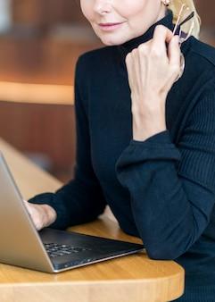Вид сбоку пожилой женщины, работающей на ноутбуке и держащей очки