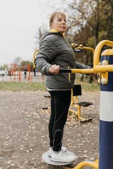 屋外で運動している年上の女性の側面図