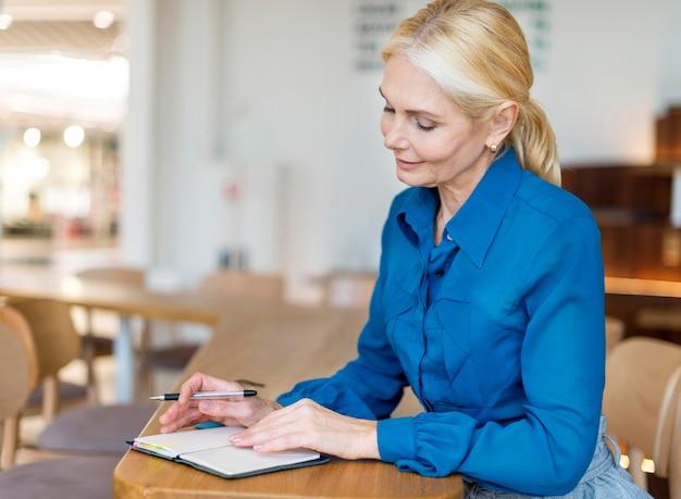 Вид сбоку пожилой женщины, работающей с блокнотом и ручкой