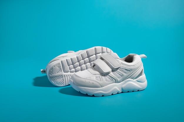 다른 신발 밑창 앞에 벨크로 패스너가 있는 흰색 남녀공용 운동화의 측면도...
