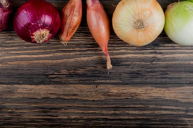コピースペースを持つ木製の背景に赤白エシャロットと甘い玉ねぎの側面図