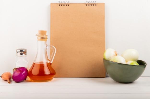Вид сбоку лука в миске растопленного сливочного масла с блокнотом на деревянной поверхности и на белом фоне с копией пространства