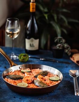 Вид сбоку паэлья с мидиями и креветками в сковороде на синем