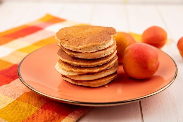 Вид сбоку блины и абрикосы в тарелке на клетчатой ткани и деревянном фоне