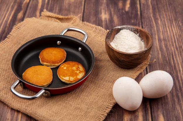 Вид сбоку на блины на сковороде и миску муки на мешковине с яйцами на деревянном фоне