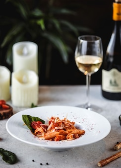 Вид сбоку макароны с томатным соусом и сыром пармезан в белой миске