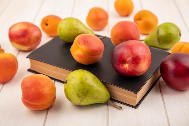 閉じた本と木製の背景に桃と梨のような果物のパターンの側面図
