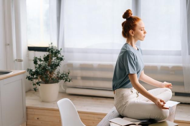 平和な赤毛の若い女性の側面図は、ホームオフィスの机に座って瞑想しています