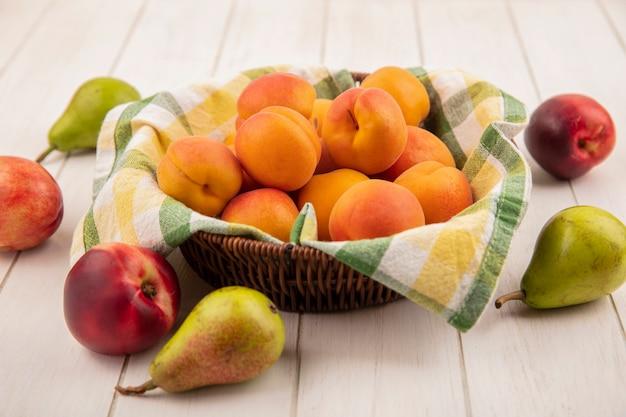 木製の背景に梨とバスケットの桃の側面図