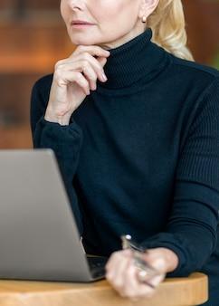 Вид сбоку задумчивой пожилой женщины в очках, работающей на ноутбуке