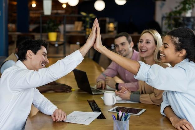 Вид сбоку на людей, приветствующих друг друга во время встречи в офисе