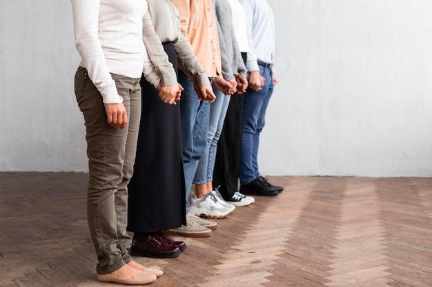集団療法セッションで手をつないでいる人々の側面図