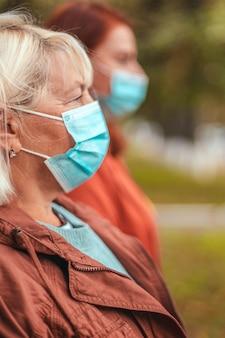 コロナウイルス、グリープ、またはプレモニアのパンデミック時に路上で保護用医療マスクを着用している人々の側面図。人混みを避ける