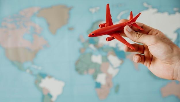 Вид сбоку человека, держащего фигурку самолета над картой