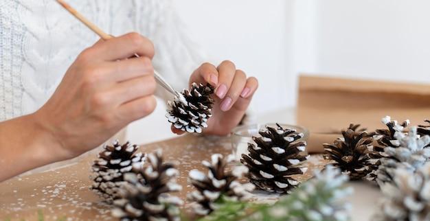 Вид сбоку человека, рисующего шишки на рождество