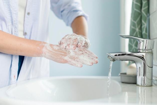 Вид сбоку лица, моющего руки в ванной комнате